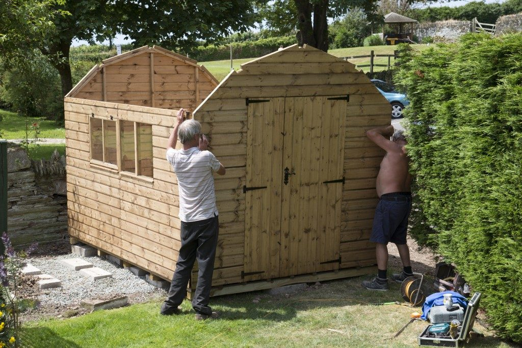 Wooden shed installation in the backyard