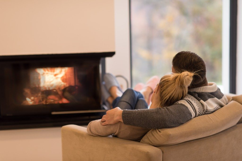 couple enjoying the company of one another by their fireplace