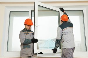 Two male builders workers at window installation