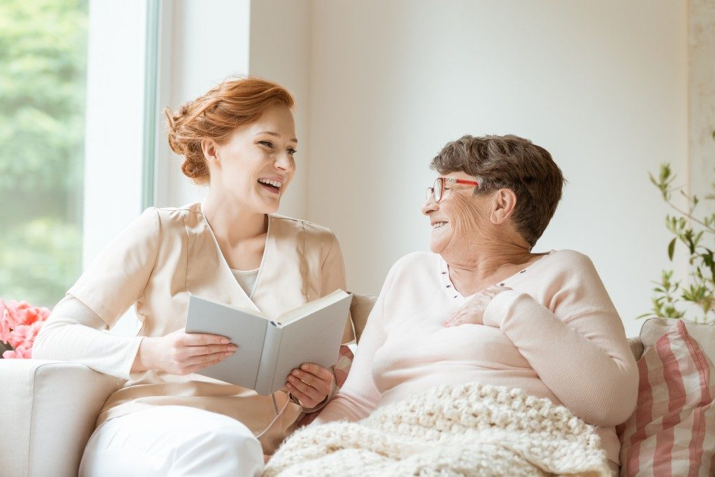 Nurse reading with elderly patient