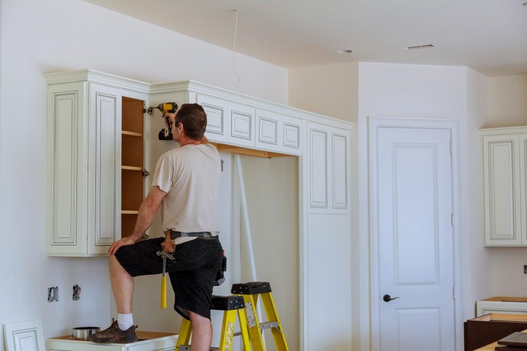 man fixing kitchen shelves