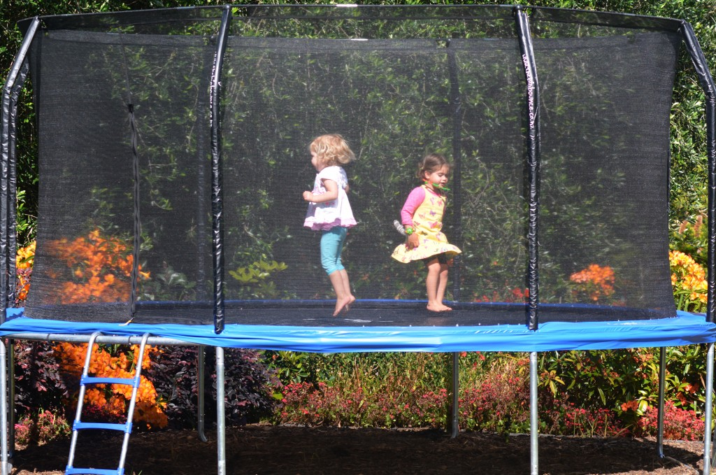 Kids jumping on the backyard trampoline
