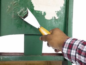 Close-up of man's hand peeling a green paint on the old chair