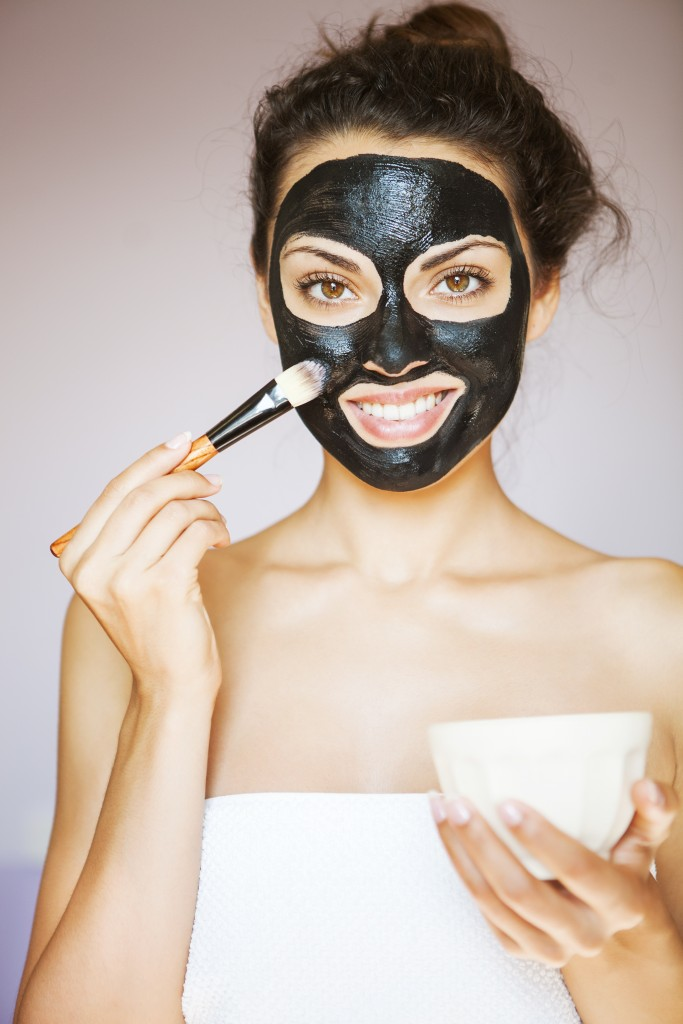 woman in towel putting a mud mask with a brush