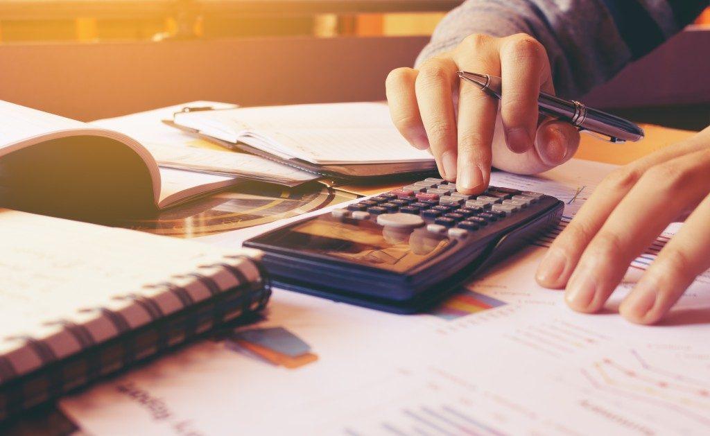 person's hand computing bills using calculator