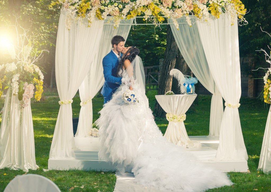 groom and bride kissing inside wedding marquee. Garden Wedding