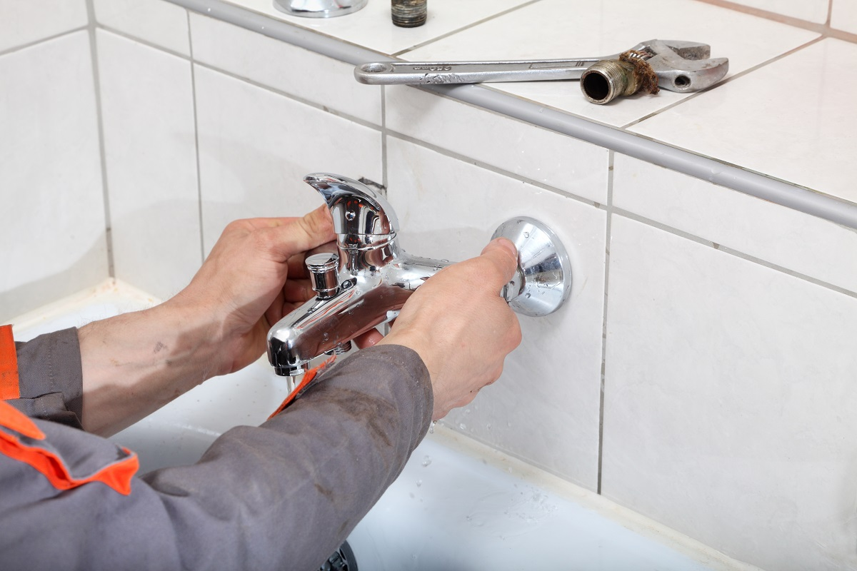 Plumber-fixing-water-tap-with-spanner