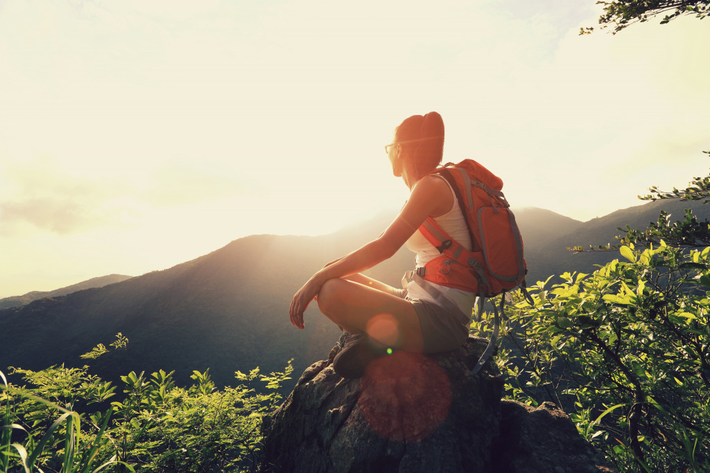 Woman backpacker sit on sunrise mountain peak cliff rock enjoy the view