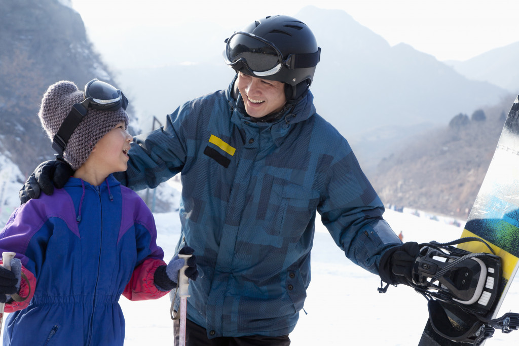 an adult helping a child to ski