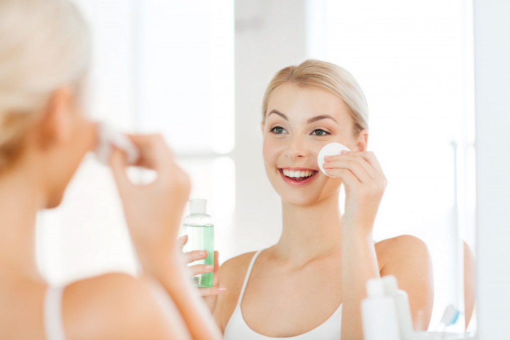 woman applying toner to her face